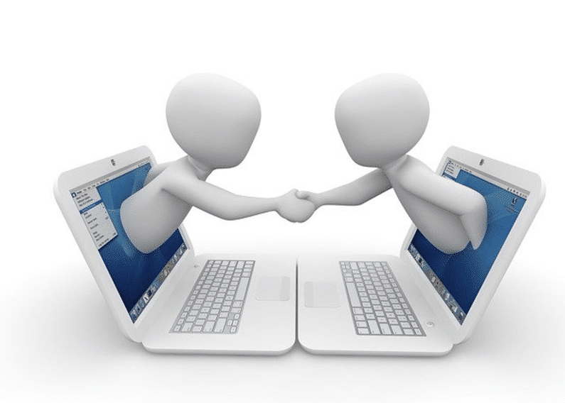 handshake extended out from two laptop screens | wordpress website | Peace Evolution