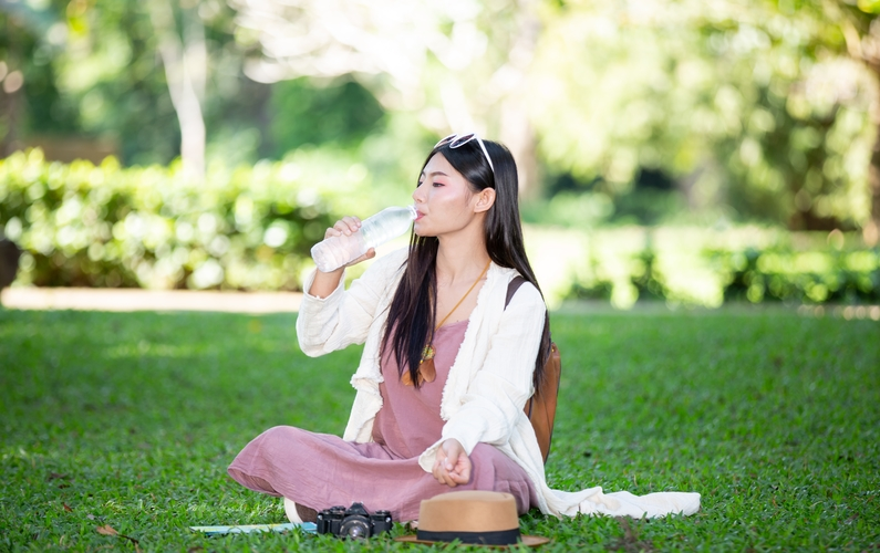 girl drinking water sitting in a park | practicing fasting | Peace Evolution