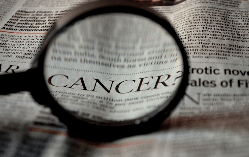 newspaper with magnifying glass highlighting the word cancer | health problems | Peace Evolution