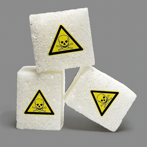sugar lumps with warning triangle | aspartame dangers | Peace Evolution