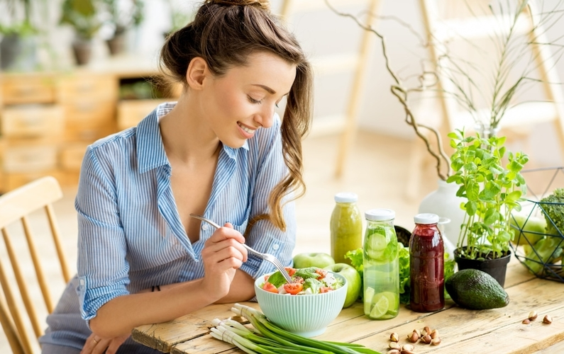 woman sitting at table eating a salad   eating vegan   Peace Evolution