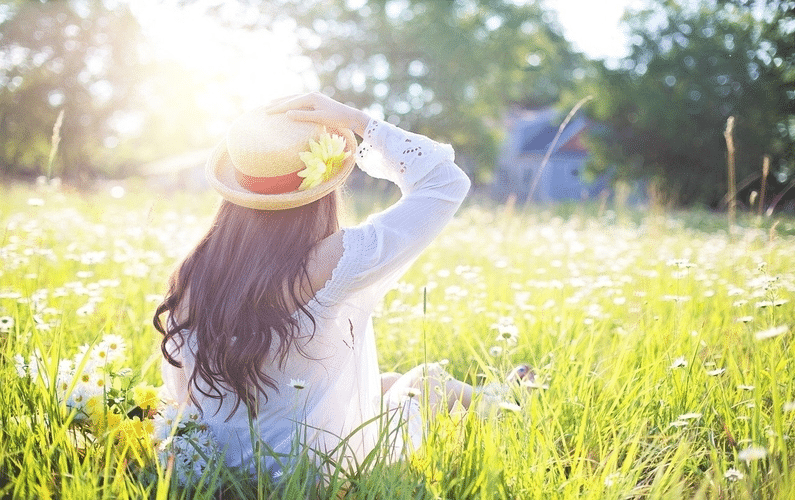young woman with straw hat sitting in field of flowers | healthy eating | Peace Evolution